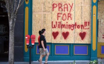 People walk by the boarded up front windows of Bourbon Street in preparation for Hurricane Florence in Wilmington, N.C., Wednesday, Sept. 12, 2018. The effects of Hurricane Florence in Southeastern North Carolina are expected to begin Thursday. (Matt Born/The Star-News via AP)