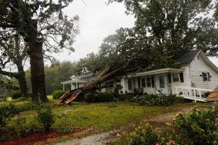 A downed tree rests on a house during the passing of Hurricane Florence in the town of Wilson, North Carolina, U.S., September 14, 2018. REUTERS/Eduardo Munoz