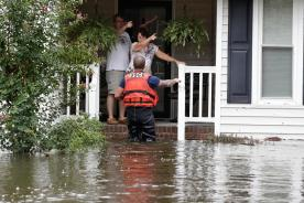A member of the U.S. Coast Guard assists Roger and Susan Hedgepeth in Lumberton, N.C., Sunday, Sept. 16, 2018, following flooding from Hurricane Florence. (AP Photo/Gerry Broome)