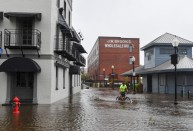 A bicyclist rides through a flooded South Water Street on Friday as Florence makes landfall in Wilmington, N.C. MUST CREDIT: Washington Post photo by Ricky Carioti