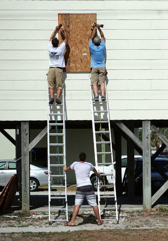 WRIGHTSVILLE BEACH, NC - SEPTEMBER 11: Workers board up a home while preparing for the arrival of Hurricane Florence on September 11, 2018 in Wrightsville Beach, United States. Hurricane Florence is expected on Friday possibly as a category 4 storm along the Virginia, North Carolina and South Carolina coastline. (Photo by Mark Wilson/Getty Images)