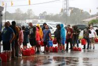 WILMINGTON, NC - SEPTEMBER 15: People wait in line to fill up their gas cans at a gas station that was damaged when Hurricane Florence hit the area, on September 15, 2018 in Wilmington, North Carolina. Hurricane Florence made landfall in North Carolina as a Category 1 storm Friday and at least five deaths have been attributed to the storm, which continues to produce heavy rain and strong winds extending out nearly 200 miles. (Photo by Mark Wilson/Getty Images)