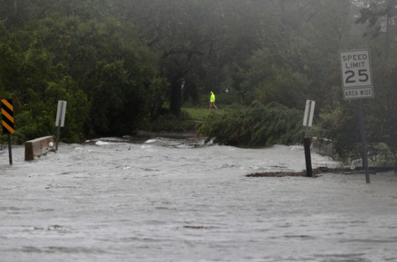 A person walks past a flooded roadway in Wilmington, N.C., after Hurricane Florence made landfall Friday, Sept. 14, 2018. (AP Photo/Chuck Burton)
